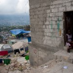 A girl sits in the doorway of one of the few structures in Port-au-Prince's Fort National neighborhood that was not leveled by the earthquake on Jan. 12, 2010. No permanent shelters have been reconstructed in the area, forcing many residents to live in tents. (Jacob Kushner for Infosurhoy.com)