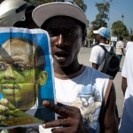 Pullos Pierre, a 26-year-old from Port-au-Prince's Cité Soleil slum, holds a picture of Aristide during a protest demanding current president René Préval steps down from power. (Jacob Kushner for Infosurhoy.com)