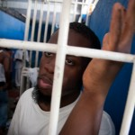 Franco Coby, who grew up in Fort Myers, looks out of the cell at the Haitian jail where he spent seven days without charge. (Photo by Jacob Kushner/FCIR.)