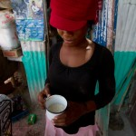 Elene Sainte Somé, 22, sells rice by the cup from her small shop in Coupon, located in Haiti's rice-growing Artibonite region. She says American rice sells better because it's processed to remove rocks and dirt. JACOB KUSHNER/Global Post