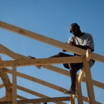 A man works to build a church roof using locally purchased, foreign-imported wood in the Neret neighborhood of Port-au-Prince. (Jacob Kushner/GlobalPost)